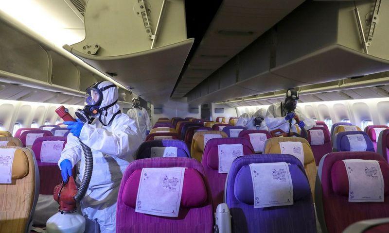 """""""Thai Airways"""" darbuotojai Bankoko oro uoste dezinfekuoja lėktuvo saloną, šitaip siekiama užkirsti kelią koronavirusui plisti. Athito Perawongmethos (""""Reuters"""" / """"Scanpix"""") nuotr."""