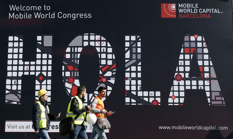"""Workers walk past a Mobile World Congress banner in Barcelona, February 22, 2013. The GSMA Mobile World Congress, representing the interests of the worldwide mobile communications industry, will take place from February 24 to 27 in Barcelona. The banner reads, """"Hello"""". REUTERS/Albert Gea (SPAIN - Tags: BUSINESS TELECOMS)"""