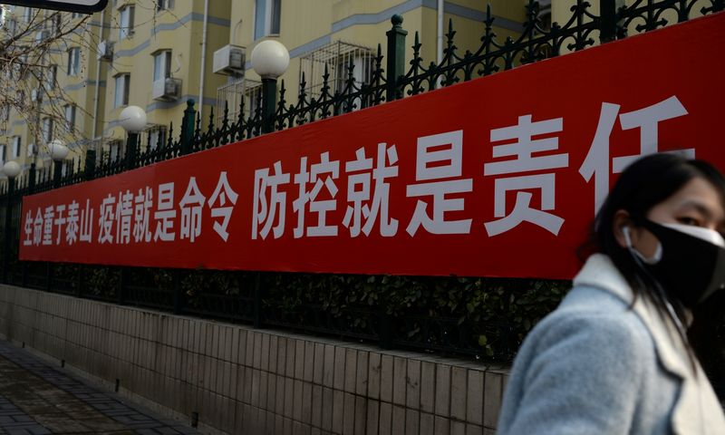 "A woman wearing a face mask walks past a banner hung outside a residential area near Beijing Financial Street, following an outbreak of the novel coronavirus in the country, in Beijing, China February 11, 2020. The Chinese characters on the banner read, ""Life weighs more than Mount Tai, epidemic is the order, prevention and control is the responsibility"". Picture taken February 11, 2020. REUTERS/Tingshu Wang"