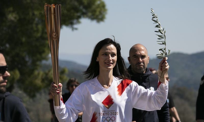 European Commissioner for Innovation and Youth Mariya Gabriel, the fourth torchbearer, holds the torch of the 2020 Tokyo Olympic Games following the flame lighting ceremony at the closed Ancient Olympia site, birthplace of the ancient Olympics in southern Greece, Thursday, March 12, 2020. Greek Olympic officials are holding a pared-down flame-lighting ceremony for the Tokyo Games due to concerns over the spread of the coronavirus. Both Wednesday's dress rehearsal and Thursday's lighting ceremony are closed to the public, while organizers have slashed the number of officials from the International Olympic Committee and the Tokyo Organizing Committee, as well as journalists at the flame-lighting. (AP Photo/Thanassis Stavrakis)