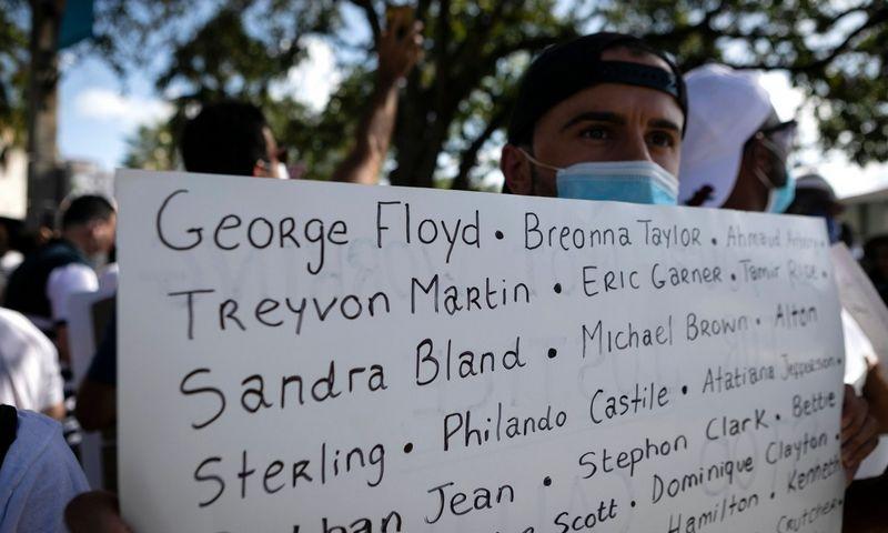 """Neramumai JAV. Protestuotojas laiko plakatą su pavardėmis asmenų, patyrusių žiaurių pwolicijos elgesį. Eva Marie Uzcategui (AFP/""""Scanpix"""") nuotr."""