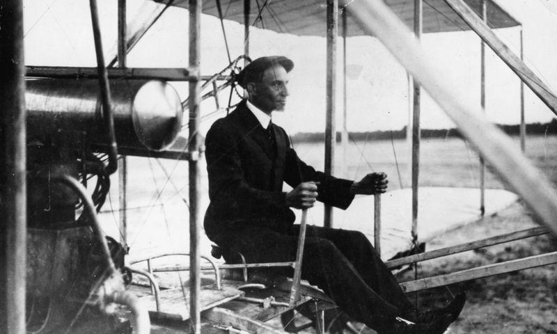"""Wilburas Wrightas, vienas iš aviacijos pionierių, savo """"skraidymo mašinoje"""", 1908 m. """"Scanpix"""" nuotr."""
