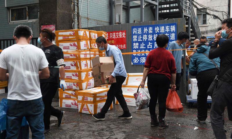 """Prekeiviai išgabena prekes iš uždaryto žuvies turgaus Pekine Greg Baker (AFP/ """"Scanpix"""") nuotr."""