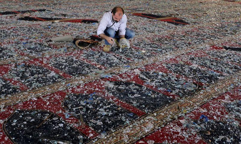 """Po sprogimo, kurio banga siekė beveik 10 km, nuo stiklų valoma mečetė. Aziz Taher (""""Reuters"""" / """"Scanpix"""") nuotr."""