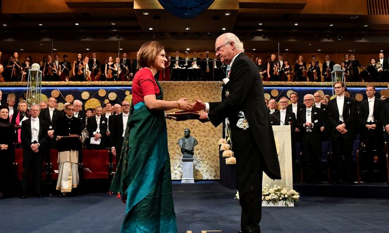 """Nobelio Ekonomikos premijos įteikimo ceremonija 2019 m. gruodžio 10 d. Stokholme: Prancūzijos ekonomistę Estherą Duflo sveikina Švedijos karalius Karlas Gustavas. Jonas Ekstromer (TT/""""Reuters""""/""""Scanpix"""") nuotr."""