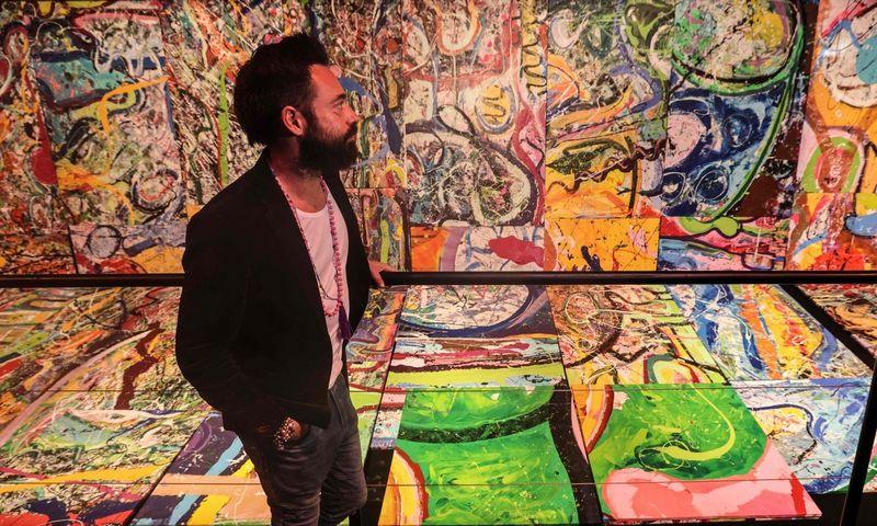 """Menininkas Sacha Jafri prie paveikslo """"Žmonijos kelionė"""" framentų. Karimo Sahibo (AFP / """"Scanpix"""") nuotr."""