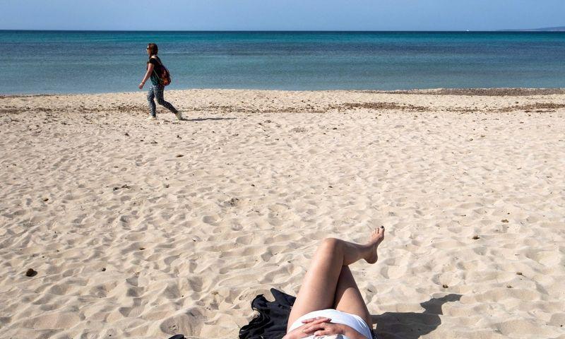 """Turistai paplūdimyje mėgaujasi saulute, Maljork, Ispanija. Jaime Reina (AFP/""""Scanpix"""") nuotr."""