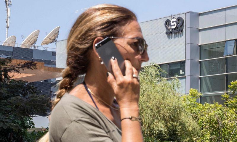 """Moteris kalba telefonu šalia """"NSO Group"""" būstinės Izraelyje 2016 m. Jack Guez ( AFP/ """"Scanpix"""") nuotr."""