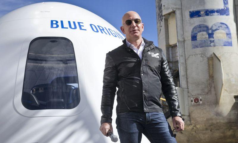 """Jeffas Bezosas """"Blue Origin"""" keleivinės kapsulės ir raketos """"New Shepard"""" fone. Chucko Biggerio (""""Scanpix"""" / """"ZUMA Press"""") nuotr."""