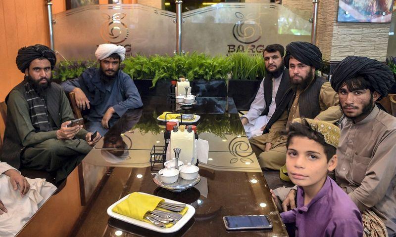 """Talibano kovotojai viename iš Kabulo restoranų. Wakil Kohsar Kabul on August 26, 2021 after Taliban's military takeover following the US troop withdrawal. (AFP/""""Scanpix"""") nuotr.)"""