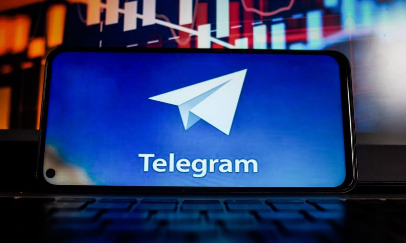 August 25, 2021, Portugal: In this photo illustration a Telegram logo is seen displayed on a smartphone with the stock market percentages in the background. (Credit Image: © Omar Marques/SOPA Images via ZUMA Press Wire)