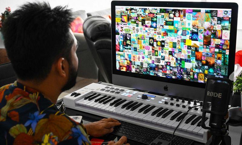 """Singapūro verslininkas Vigneshas Sundaresanas žiūri į Mike'o Winklemanno sukurtą koliažą """"Everydays: The First 5,000 Days"""". Jį kaip nekeičiamąjį žetoną V.  Sundaresanas įsigijo už 70 mln. USD. Roslano Rahmano (AFP / """"Scanpix"""") nuotr."""
